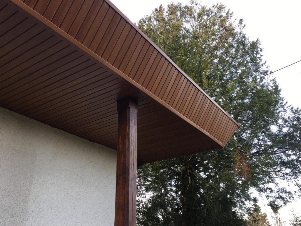 pose d'un bardage en bois foncé sur le avant-toit